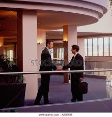 two businessmen shaking hands on mezzanine interior of modern office building stock image agri office mezzanine