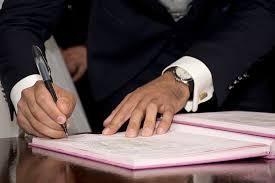 the shifting healthcare cfo role career challenges in centralized man in suit signing his to a book